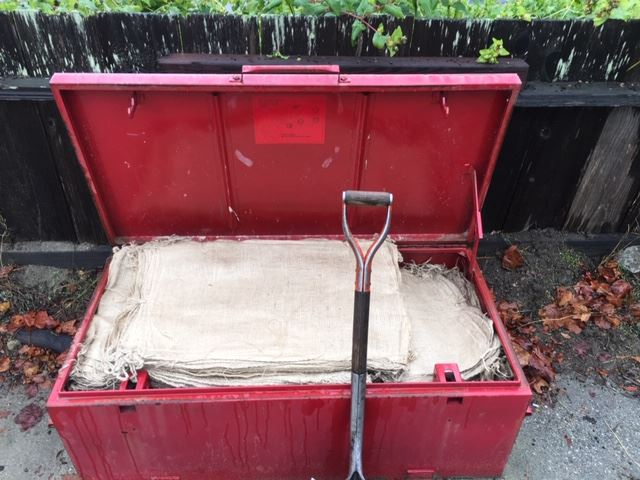 Picture showing red box with sandbags and shovel.